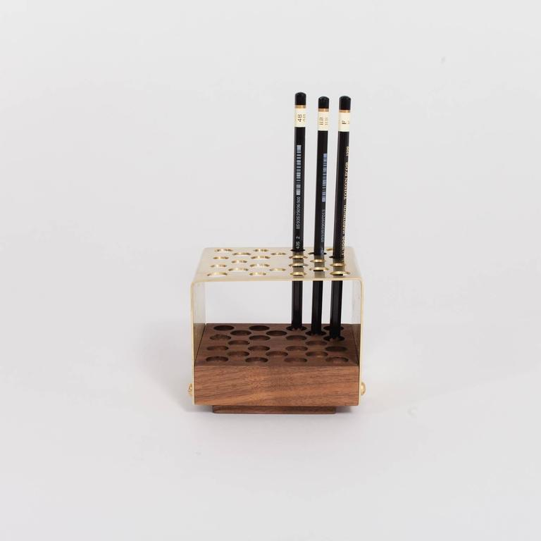 Designed to accompany our Physalia desk and Physalia desk folio, our pencil holder is made of hand machined brass. It comes with three options for the wooden base: American walnut, ebonized maple, or fog gray ash.  The pencil holder would befit