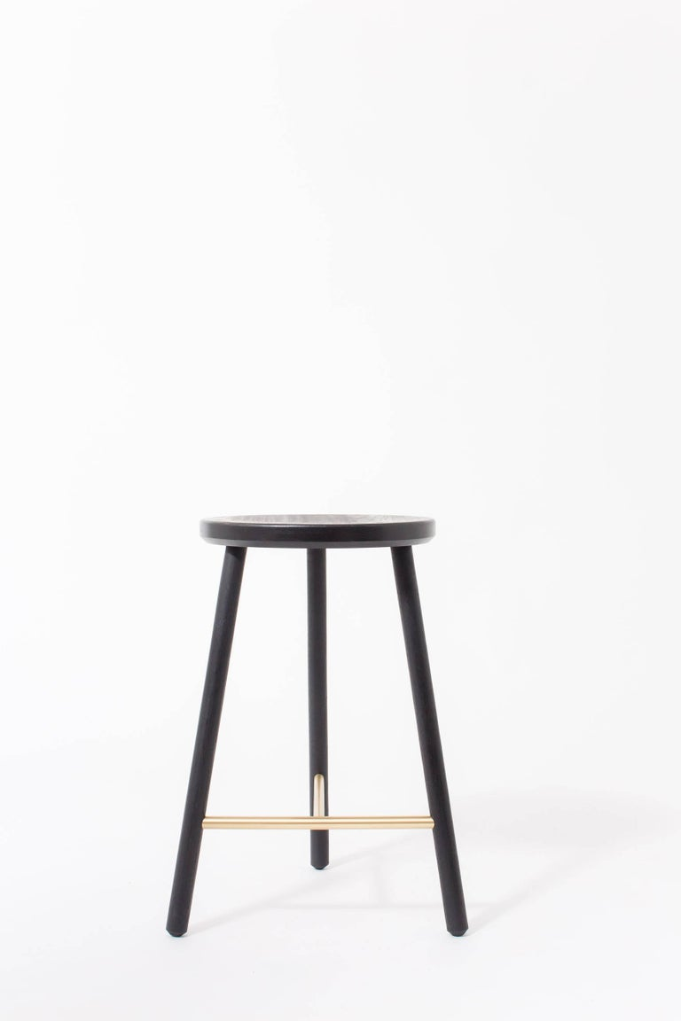 The scout stool has a slim design, allowing it to be tucked into small spaces with a minimal footprint. Offered in walnut, cerused oak, and ebonized oak with satin brass or satin nickel accents. Custom sizing and finishes available upon