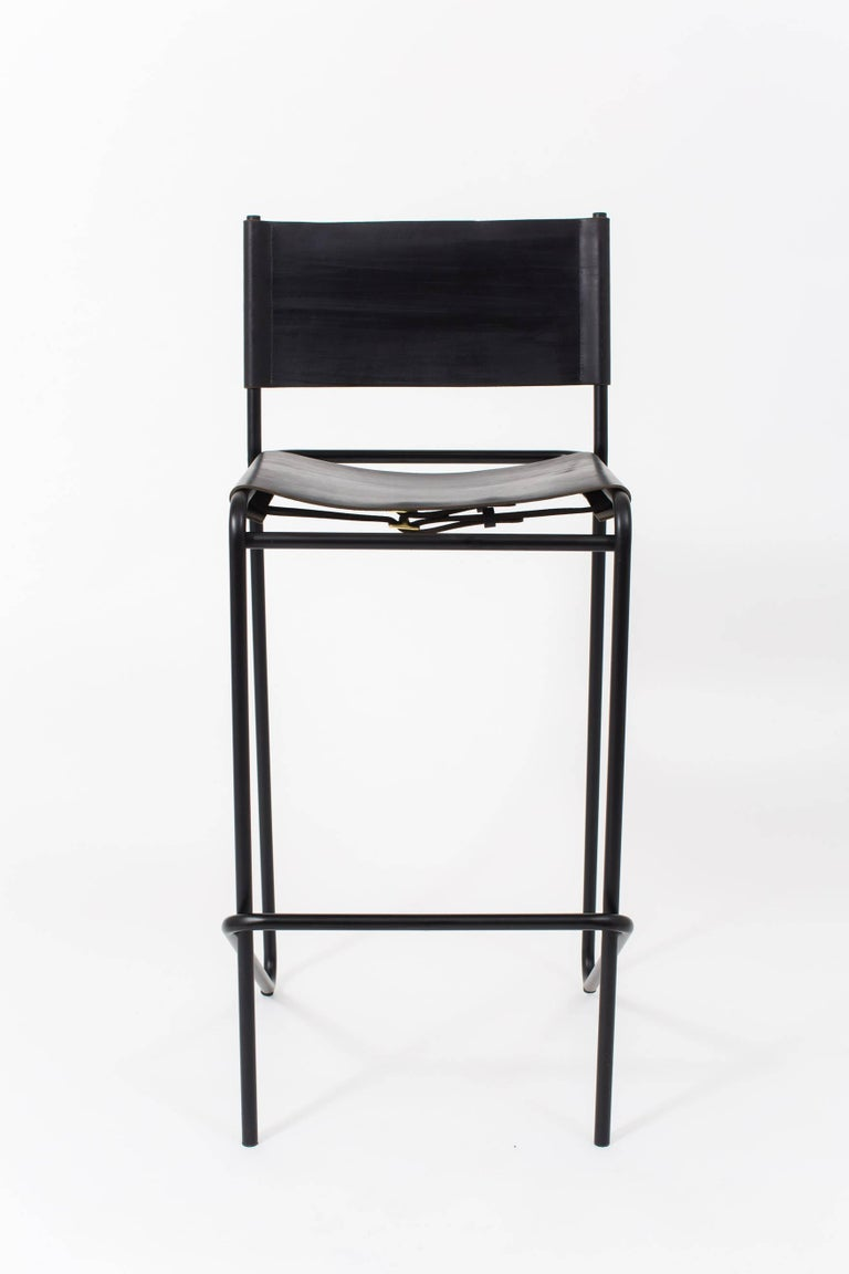 The Flora Bar stool is composed of just three pieces of steel: an L-shaped back piece that touches the floor and rises up again at an angle to create a footrest; a rectilinear seat and front support; and a simple, stabilizing cross-bar across the