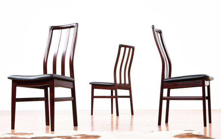 Set of six outstanding vintage 1980s Scandinavian rosewood dining chairs. These chairs feature ergonomic design with a contoured back to support the natural curve of occupant's body. The rosewood is absolutely stunning with a deep red hue and sleek