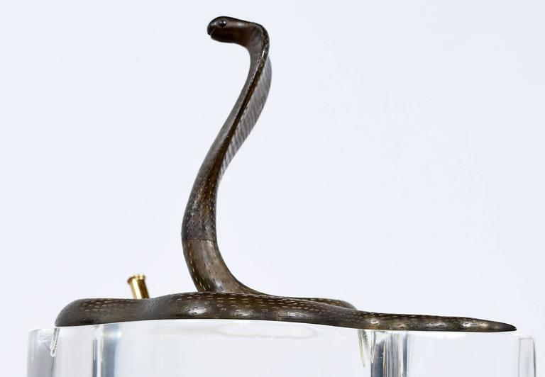 Vintage Lucite and brass double pen holder from the 1970s. This unique sculptural piece features a large brass king cobra sitting atop a thick V-shaped Lucite base with a brass pen holder on each end. It's signed by the artist on the back.