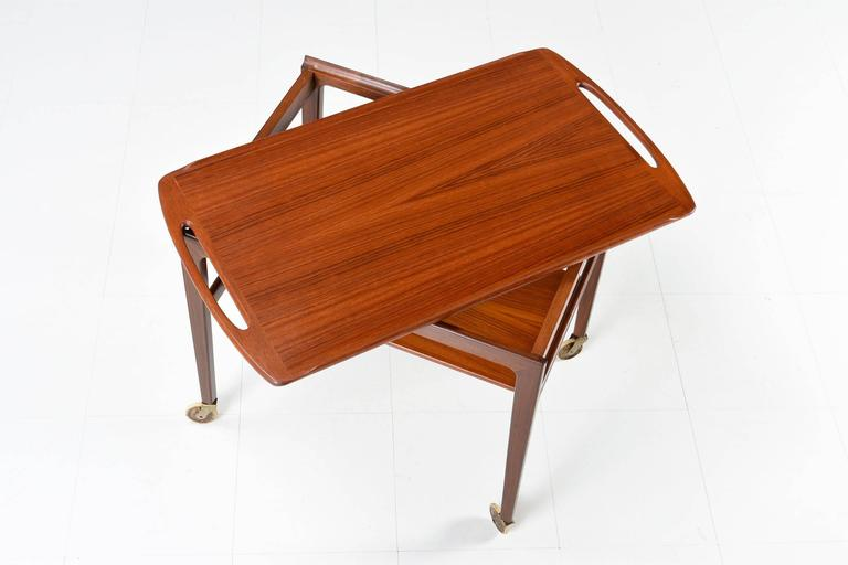 Beautifully sculpted Danish modern tray top teak tea or bar cart, model #263, made by Anton Kildebergs Møbelfabrik, 1964. This cart has a unique feature, the top lifts out doubling as a serving tray. It has a second shelf, mounted just below the