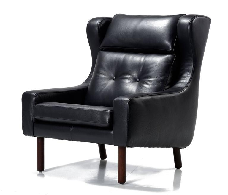 Luxurious pair of black leather Mid-Century Modern 'His & Her' armchairs. These chairs had no marking, but they are clearly in the style of Frits Henningsen and Svend Skipper, made in the 1960s. The larger chair has a wingback style, high back and