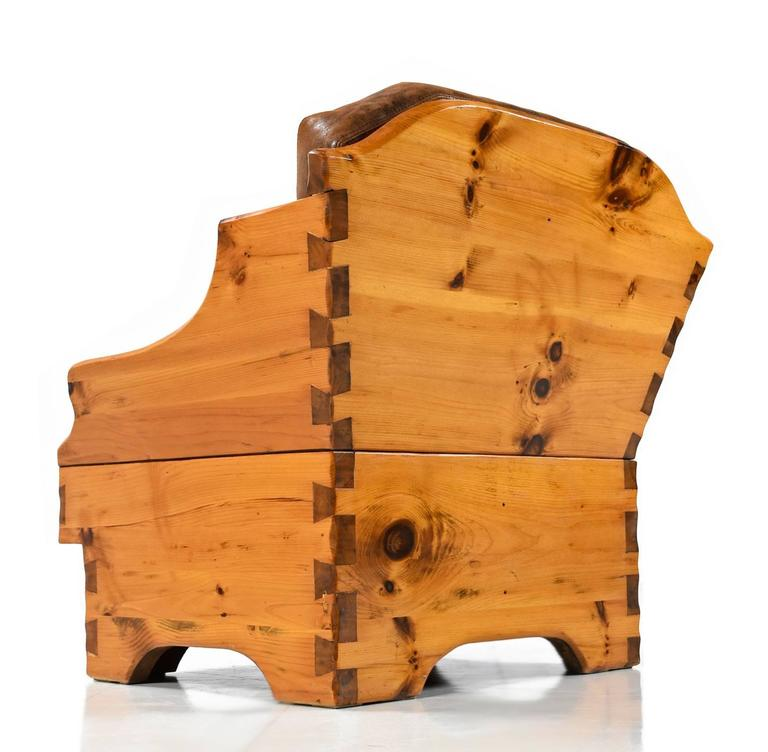Restored solid pine handcrafted, one of a kind armchair. The masterful craftsmanship is left exposed as a design element. Large dovetail joints are a darker tone, enhancing their presence. The thick planks of knotty pine are sure to last many more