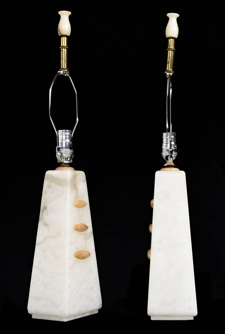 Acquired from the original owner who purchased them in the mid-1950s in New York City. Solid, heavy alabaster cut into an angled pyramid shape. Three stacked oval amber colored alabaster relief pieces extend from the faces of each lamp. The style of