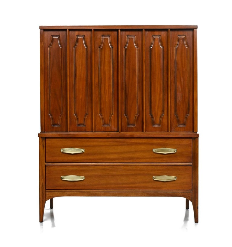 This gorgeous gentlemen's dresser created by Kent Coffey for the Marquee Modern line boasts a beautiful finish that celebrates its walnut grain. The top portion features two cabinet doors that open up to three large drawers for storage. Below are
