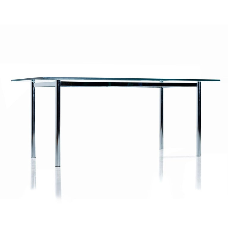 Vintage 1970s chrome base dining table with large, thick, rectangle glass top. Contoured chrome spanners bow inward and anchor into the thick tubular legs of the table base. Minimalist design combined with architectural construction allows the