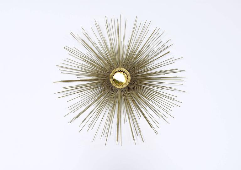 This striking Mid-Century Modern large sunburst wall sculpture is in the style of Curtis Jere, circa 1970s. The wall sculpture is three-dimensional and has three layered tiers of metal spikes radiating out from a polished brass centre. In excellent