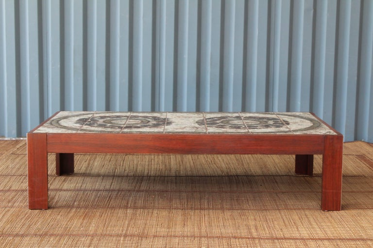Danish modern coffee table with a beautifully designed glazed tile top. The edges of the legs feature an interesting inlaid metal detailing. Signed 'Ox Art 78'.