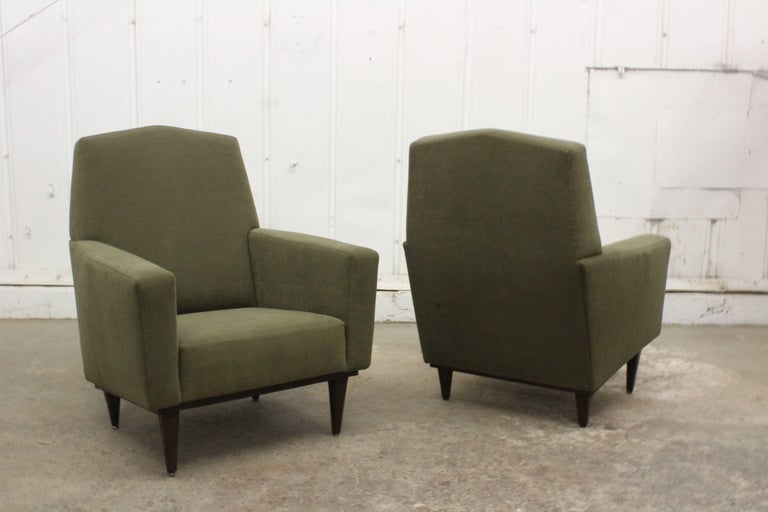 Pair of 1950s French armchairs with modern lines and walnut legs. The pair feature a soft new olive green chenille upholstery.