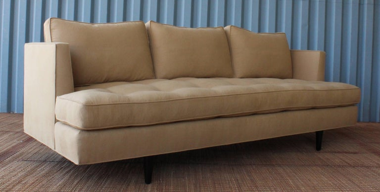 1950s Mid-Century Modern sofa in the manner of Edward Wormley. Features new upholstery and satin black wooden legs.
