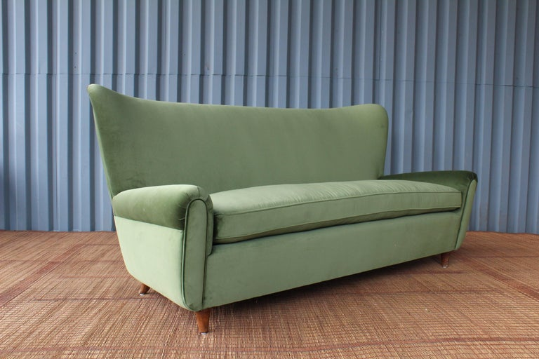 A stunning 1950s Italian modern wing back sofa. Freshly upholstered in a luxurious olive green velvet. In the manner of Paolo Buffa.