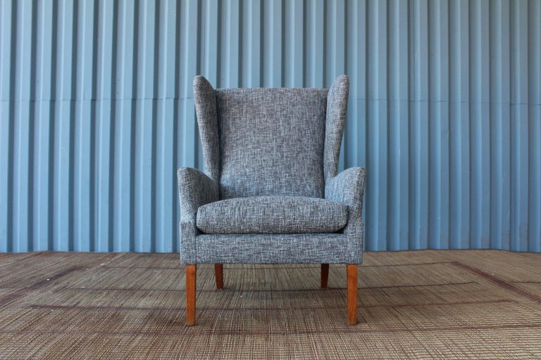 1960s Danish high back armchair newly recovered in a textural charcoal grey upholstery.