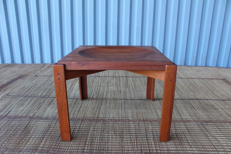 A Danish made side table in solid teak. Features a reversible teak wood top, one side flat and the other side concave. Designed by Jens Quistgaard, Denmark, 1960s.
