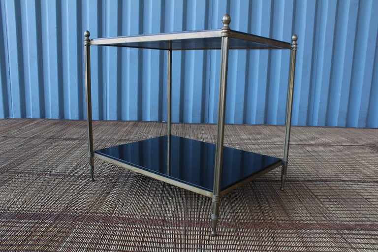 Solid brass two-tiered side table with black granite tops, France, 1950s. Excellent condition with age appropriate patina to the brass.