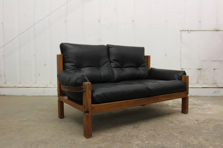Loveseat designed by Pierre Chapo, France, 1950s. Frame constructed in solid elm and new black leather cushions with original leather straps and hardware.