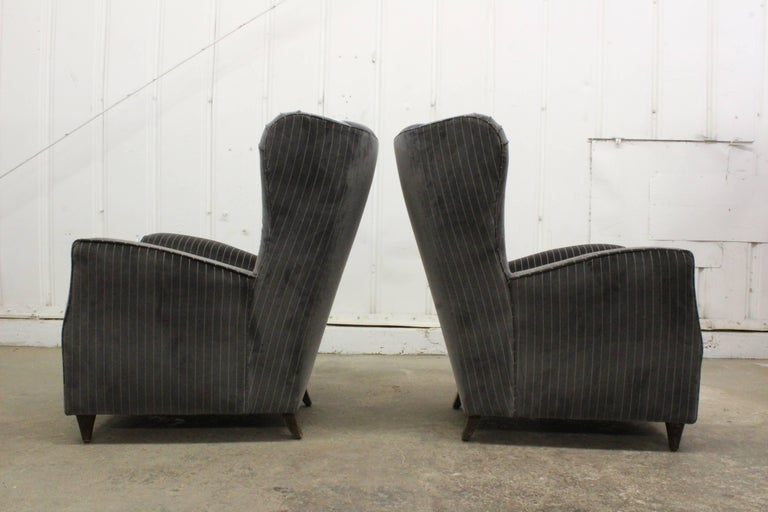 Pair of high back armchairs by Paolo Buffa, Italy, 1950s. The pair has been recently upholstered in a grey and beige pinstripe velvet. Original wear on the walnut legs.