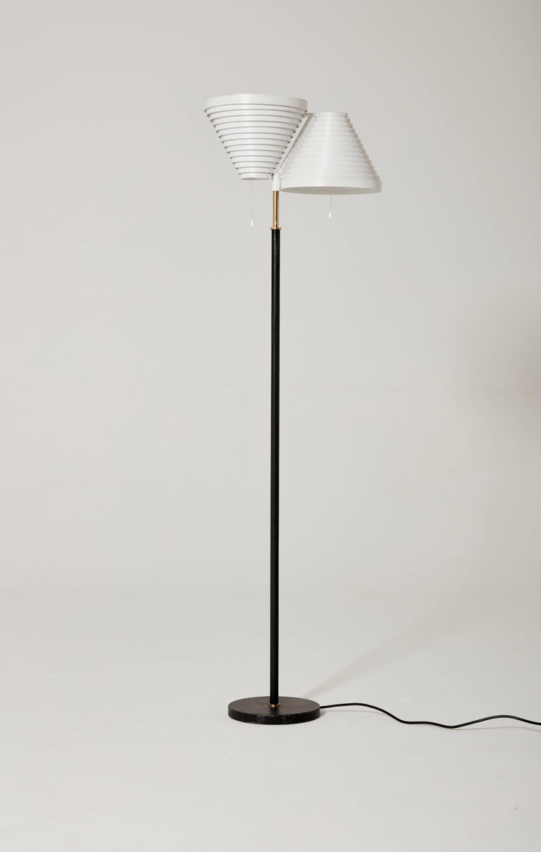 Alvar Aalto A810 floor lamp, produced by Valaisinpaja Oy, Finland with makers mark. White painted metal double shades. Brass stem and leather bound stem and base. Very good vintage condition with minor signs of use and wear. Ships worldwide.     UK