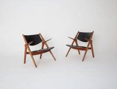 A pair of Hans Wegner CH 28 Sawbuck Armchairs, 1950s, Denmark