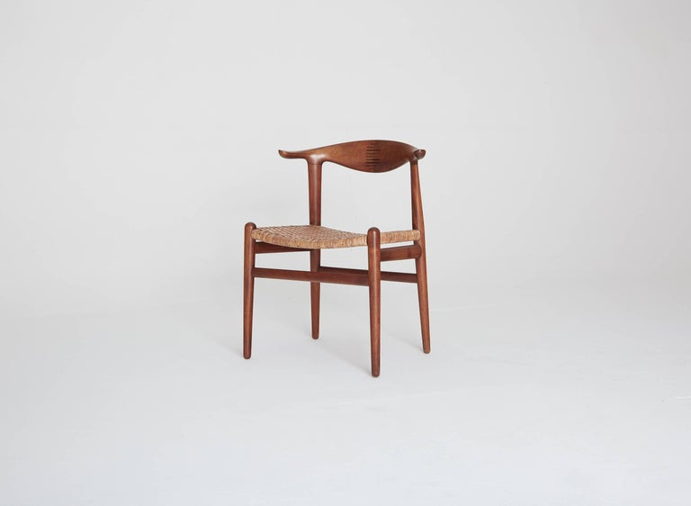 Hans Wegner cow horn (Kohornstol) chairs model JH 505, made by Johannes Hansen, Denmark. Teak and rosewood inlay, with cane seat.
