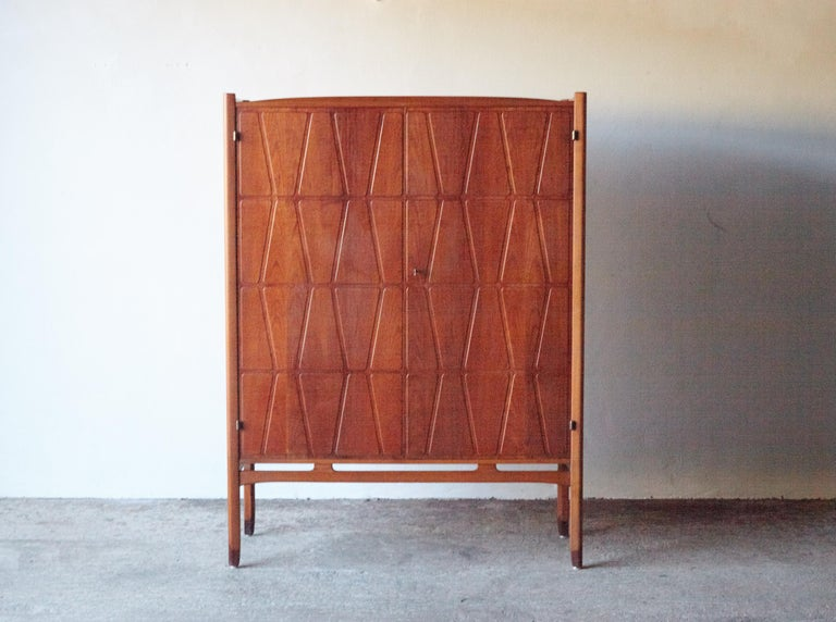 A wonderful Bangkok cabinet designed by Yngve Ekström for Westbergs Mobler, Sweden, 1950s. Solid beech legs with teak doors and sides. Inside there are three drawers and adjustable shelves. Very good vintage condition with key present.