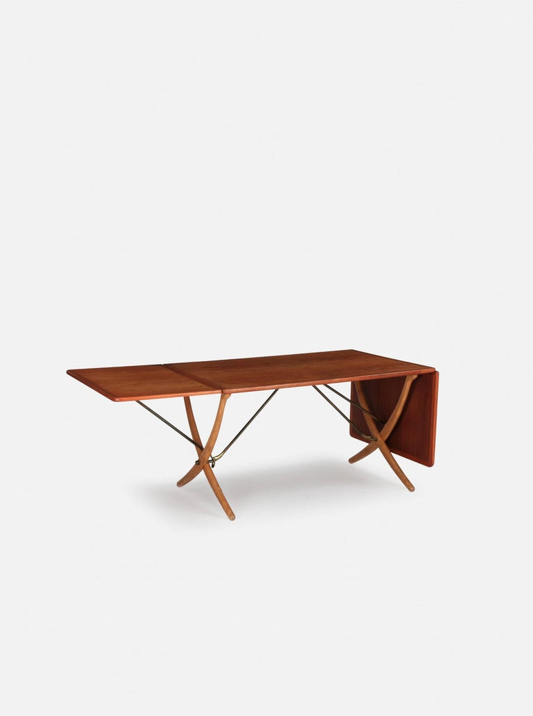 Hans Wegner AT 304 dining table, made by Andreas Tuck in Denmark, 1960s. Teak with beech cross legs and brass bars. Two flip up / extendable leaves. Length is 128cm unextended, 178cm with one leaf up and 238 cm with both leaves extended. Width 86