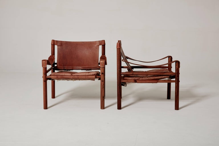 An exceptional original pair of Arne Norell safari sirocco chairs in rosewood and patinated brown leather, 1960s, Sweden. Made by Norell Möbel, AB, Sweden.