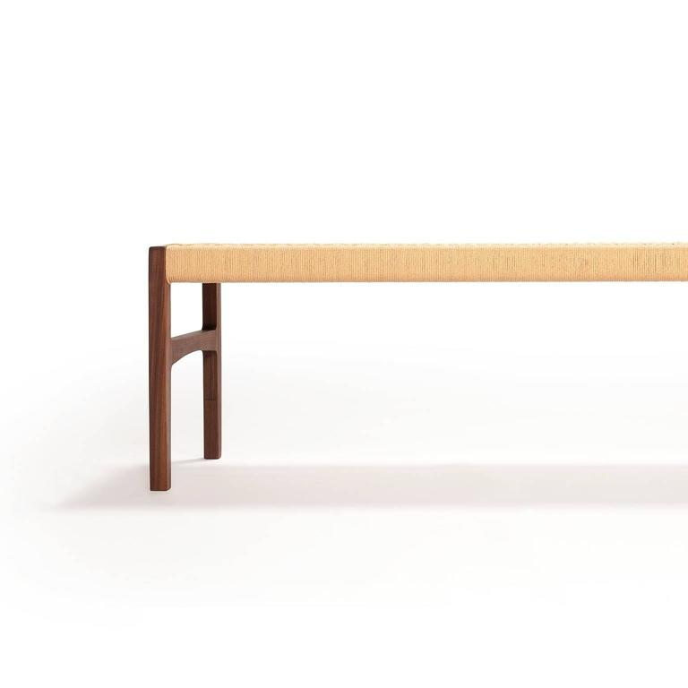 A bench with subtle curves in solid walnut with woven danish cord seat, perfect for use in the bedroom, hallway, living space or kitchen.