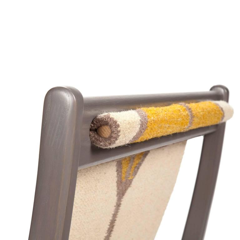 Ash lounge chair with gray stain, woven wool rug sling seat.