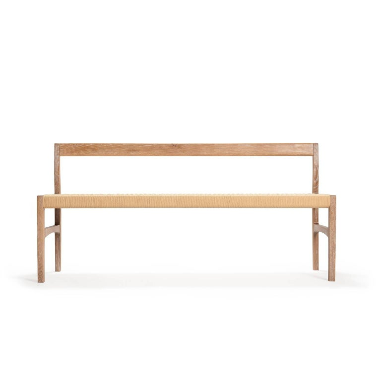 A bench with subtle curves in solid white oak with woven danish cord seat, perfect for use in the bedroom, hallway, living space or kitchen.