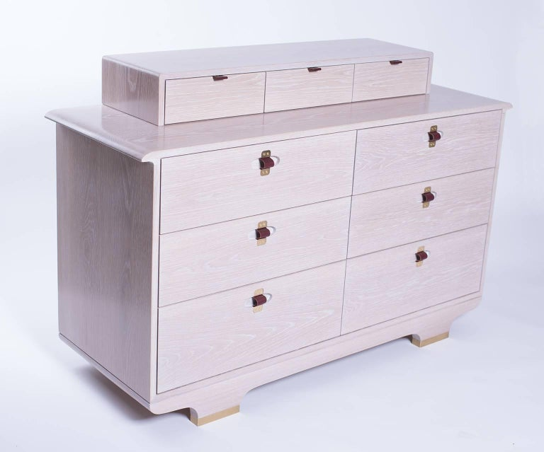A nine drawer chest in white oak, with a whitewashed finish, brass/leather pulls, and brass feet. Also available without top row of small drawers.