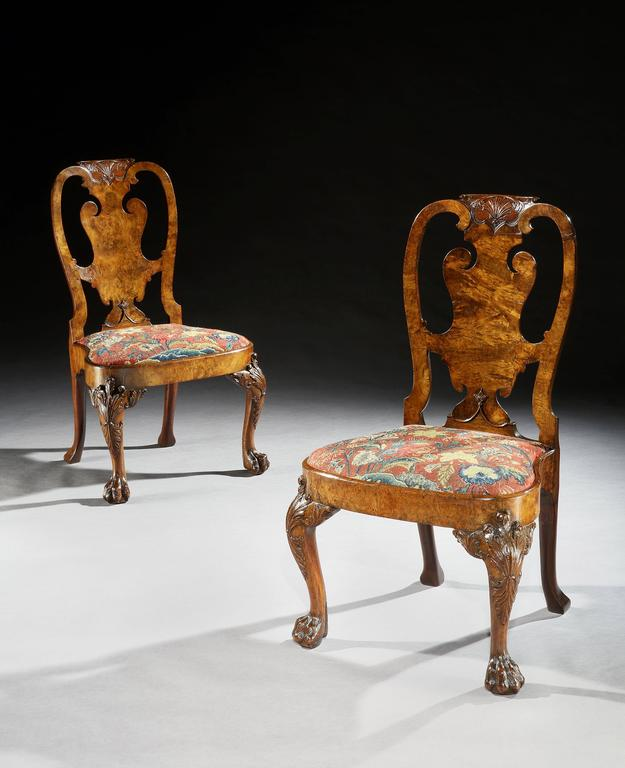 An important and very well documented pair of early George II side chairs in well figured veneered walnut and burr walnut, the carved shaped top rails centered by a shell above a shaped splat and with shaped seats covered in floral gros point and