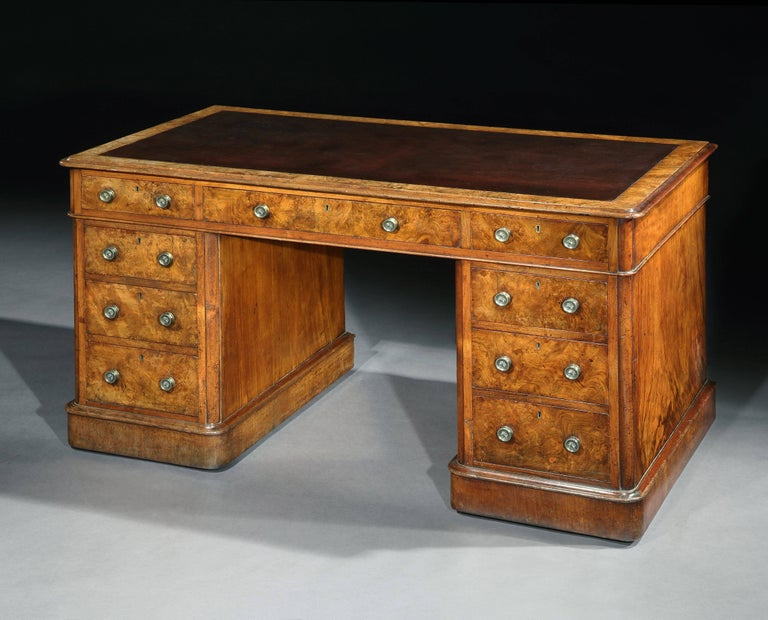 """A Victorian burr walnut pedestal desk, the moulded top with an inset panel of tanned leather, on a moulded plinth ? English, circa 1860  Measures: Width 53 """" 136 cm  Depth 26 ½ 67 cm  Height 31"""" 80 cm."""