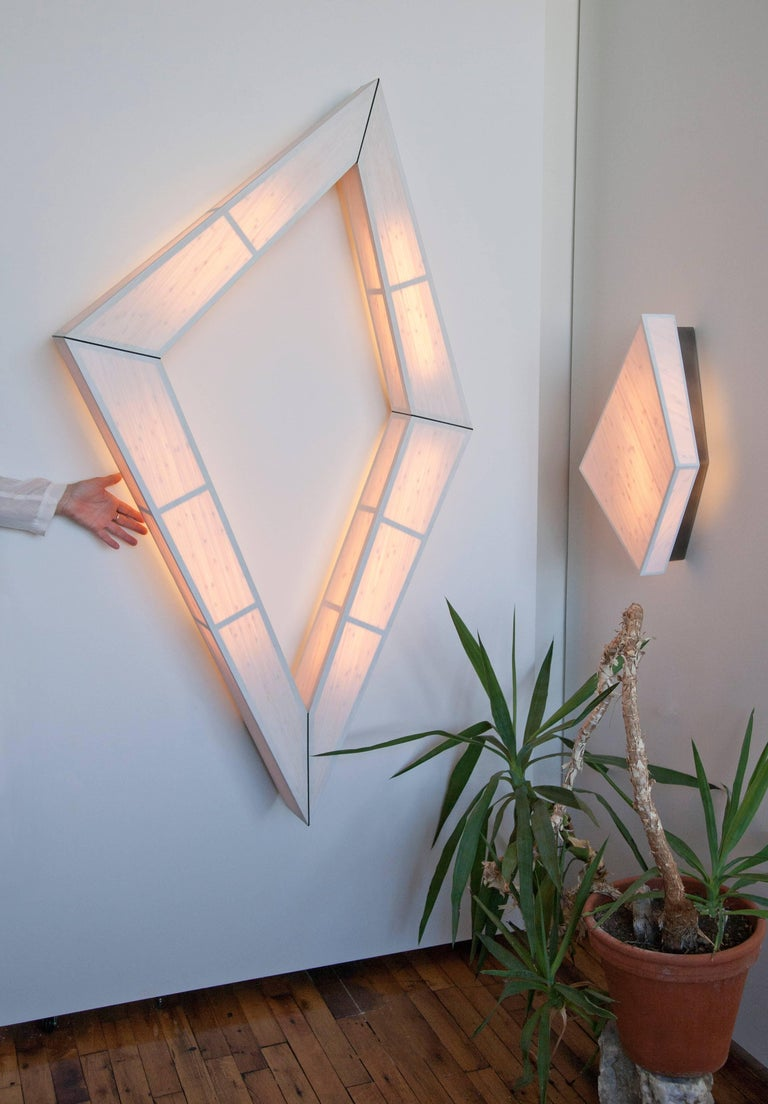 Hand-made in Brooklyn, the Diamond Illuminate is a large geometric wall or ceiling mounted lighting piece. The shape is a glowing eccentric diamond outline.  Its made of paper backed bamboo mounted on laser cut recycled-paper board, with a brass