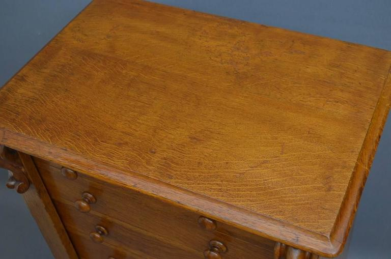 Sn3162 Victorian Wellington chest of drawers in oak, having moulded top and seven graduated drawers all fitted with original turn knobs, flanked by drop carving and locking bars with original, working lock and key, all standing on plinth base. This