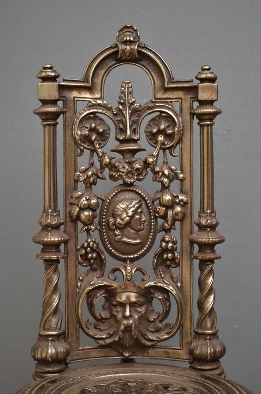 Sn4133, very decorative pair of cast iron chairs, having tall backs with pierced foliage design flanked by twisted columns and intricate medallion seats, standing on cabriole legs. Measures: H39