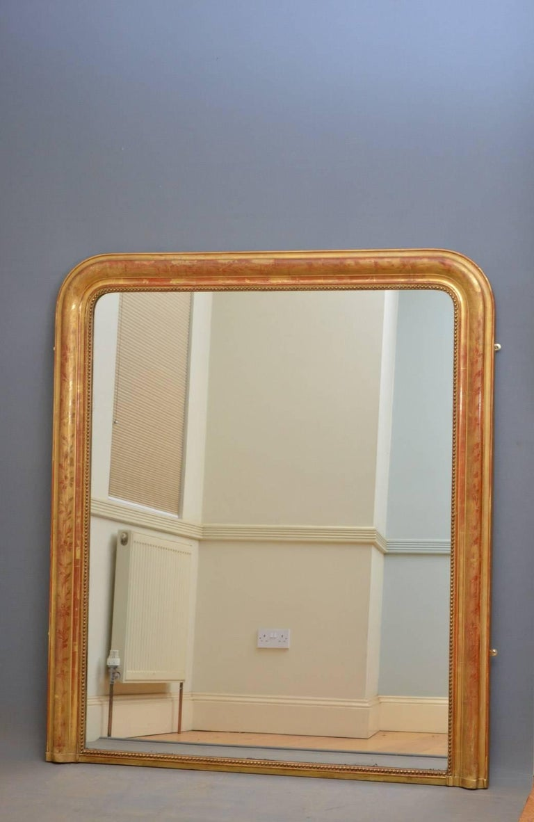 Sn4268 French giltwood overmantel mirror, having original mirror plate with some foxing in moulded frame decorated with flowers and leaves. This antique gilded mirror is in fantastic original condition throughout, ready to place at home, circa