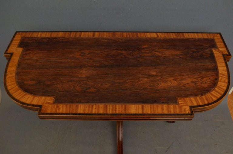 Sn4479, exceptional Regency rosewood games table, having attractive satinwood crossbanded shaped top with finely inlaid edge, enclosing clean baize gaming surface, raised on turned and reeded column terminating in 3 reeded legs, paw feet and
