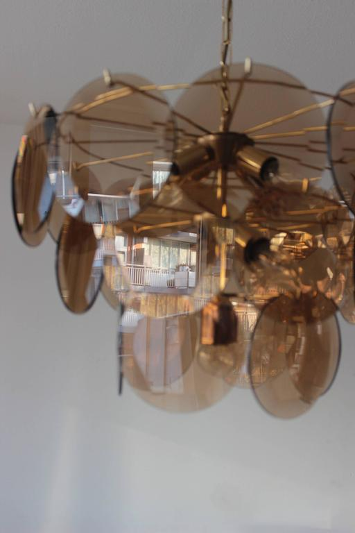 Vistosi smoked glass disc, and brass chandelier from Italy, 1970s.