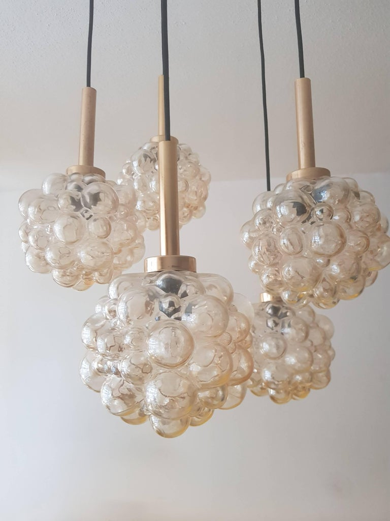 Bubble chandelier by Helena Tynell a designer from Finland. This design is from the 1960s. The chandelier has 5 lights with glass shade of iridescent, amber-colored bubble glass, hangs on an elegant brass linkage