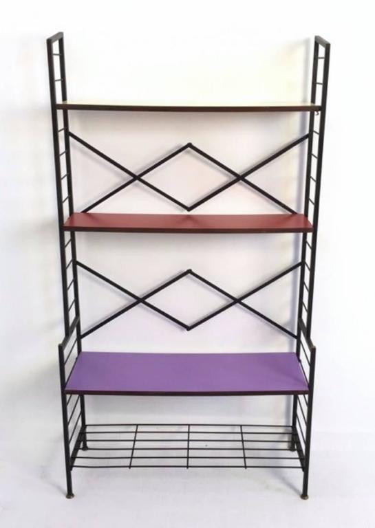 This shelving unit is made from varnished iron with brass feet caps and wooden shelves that are covered in Formica.
