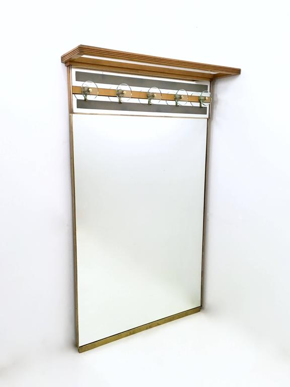 Made from mirror, brass, glass and wood. 