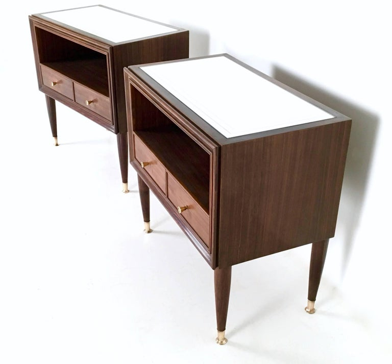 These two high-quality nightstands are made in mahogany and feature a mirror top and brass handles and feet caps. 