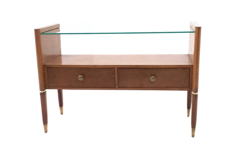 It is made in walnut and features a glass top and brass parts.