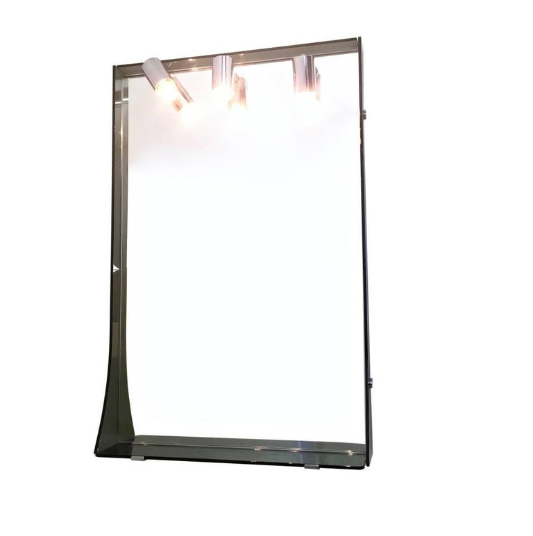 Made in mirror, smoked glass and chrome-plated metal. It features 3 working lights and its original wiring. It has no breaks, but the top may show slight traces of oxidation. In good original condition and with its original labe.  Measures: