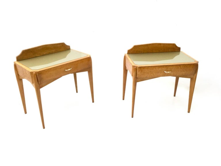 They are made in birch and beech. They feature a back-painted glass top and brass feet caps and handles. They have been restored and polished with shellac, therefore they are in excellent condition and ready to become a piece in a