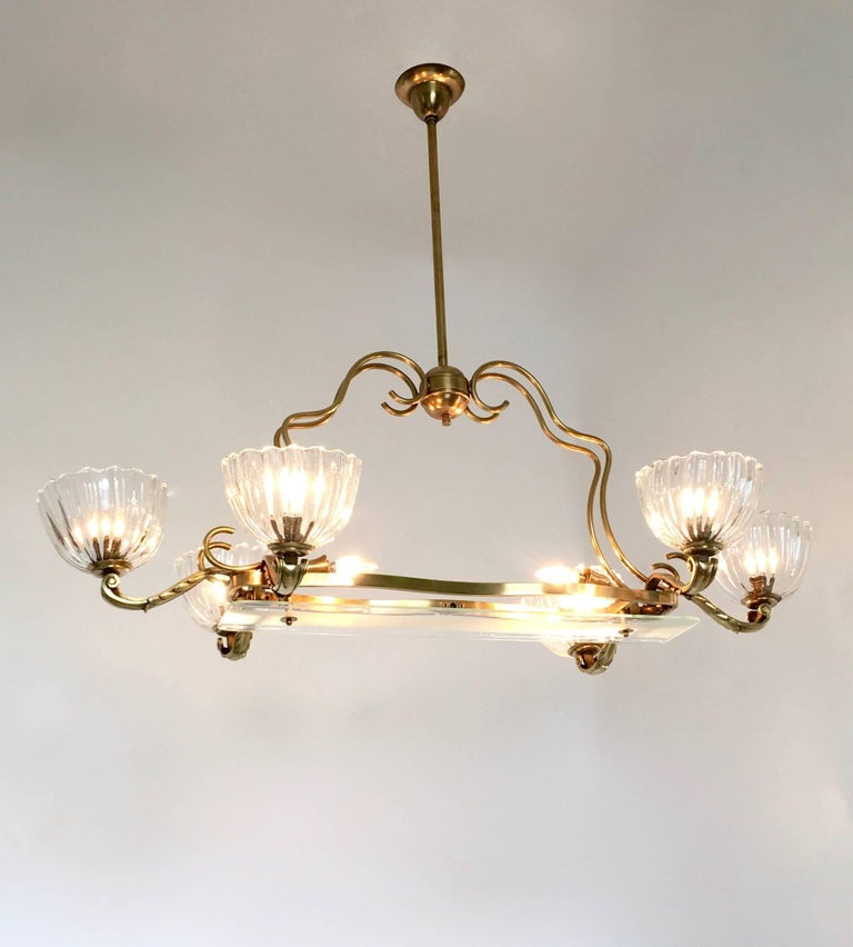 This chandelier features eight lights and a brass structure with cast brass details. It has six Murano blown glass diffusers and a frosted glass screen that has decorative motifs and functions as a lampshade for the other two lights. This