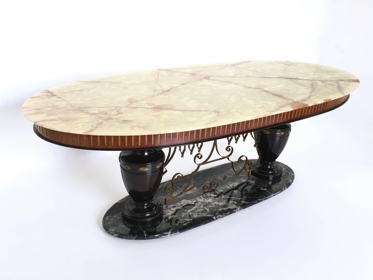 This majestic table is made from onyx and Portoro marble, sitting on turned legs made from lacquered wood, and featuring brass and metal finishing. The edge is made in wood.