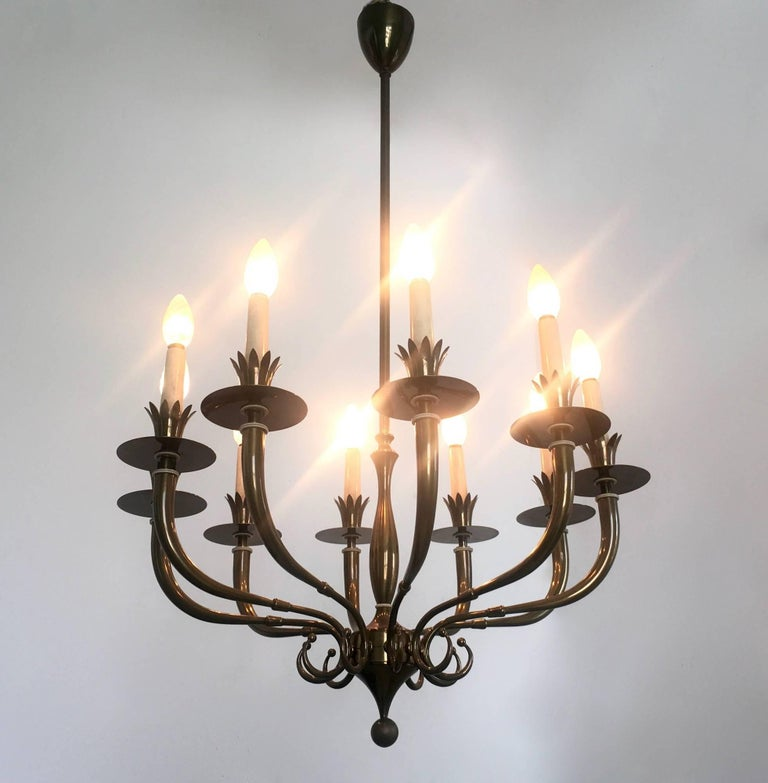 This chandelier is made in brass and lacquered wood.  It may show slight traces of use, but it is in excellent original condition and it is ready to give a beautiful ambiance to any room.   Measures: Diameter 61 cm Height 98 cm.