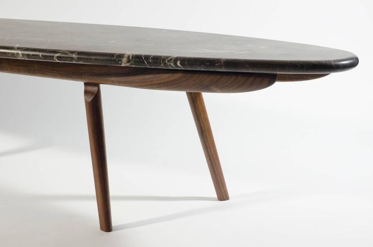In a similar spirit to the skip table, the Wendel table's form is inspired by hydrodynamics. Like a large stone in a moving body of water, the Wendel Table holds its place in any setting. The honed black marble and oiled walnut give a strong